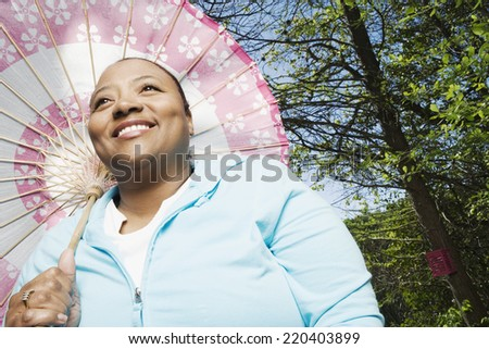 African woman with parasol outdoors - stock photo