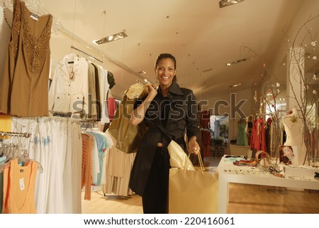 African woman with shopping bags at boutique - stock photo