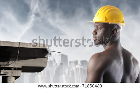 African worker beside broken concrete structure and cityscape on the background - stock photo