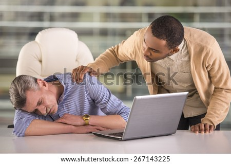African worker waking his sleeping senior colleague in office. - stock photo