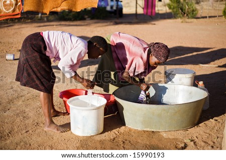 african young girl and an elderly woman washing clothes in the yard - stock photo