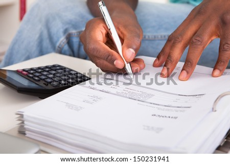 African Young Man Calculating His Finance Expenses At Home