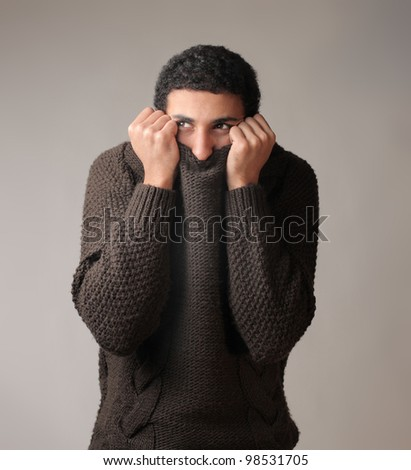 African young man hiding his face in his pullover - stock photo