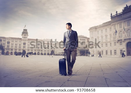 African young man holding a suitcase in a square
