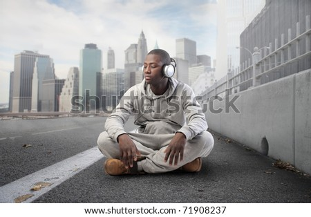African young man listening to music on a city street - stock photo