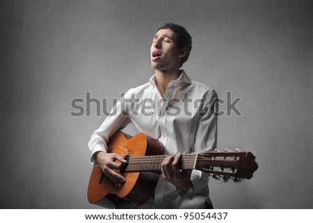 African young man playing the guitar and singing - stock photo