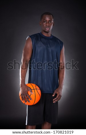 African Young Man With Basketball Over Black Background - stock photo