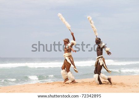 african zulu man dancing on beach - stock photo