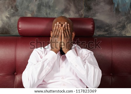 Afrikan man in pink shirt covering face with hands while sitting on red leather sofa