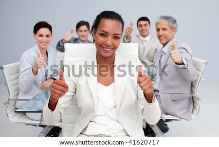 Afro-American businesswoman and her team with thumbs up in the office - stock photo