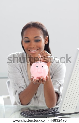 Afro-american businesswoman saving money in a piggybank at her desk - stock photo