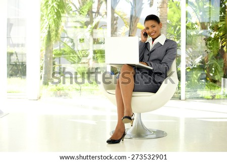 Afro American businesswoman using laptop on knees and giving a phone call with smartphone in a lobby - stock photo