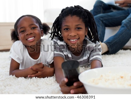 Afro american children watching television and eating pop corn in the living room