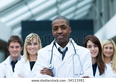 Afro-American doctor leading his team with folded arms and looking at the camera - stock photo