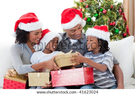 Afro-American family holding Christmas gifts at home - stock photo