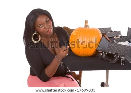 Afro-American female make up artist applying makeup on Halloween carved pumpkin (Jack O' Lantern) - stock photo