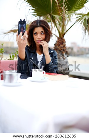 Afro american female taking fun self portrait with smart phone camera while sitting at cafe terrace near the beach, attractive hipster young woman taking a picture of herself on her cell phone - stock photo
