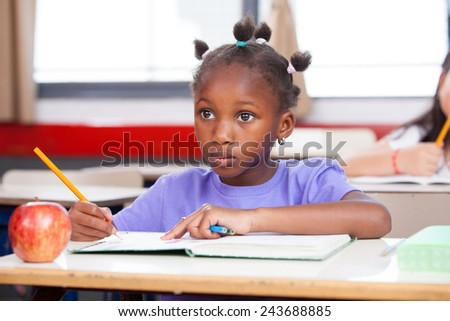 Afro american girl in primary school classroom writing her book. - stock photo