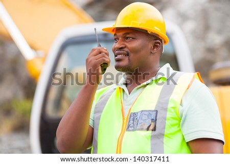 afro american industrial worker talking on walkie-talkie at mining site - stock photo