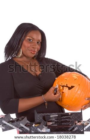 Afro-American make up artist applying makeup on Halloween carved pumpkin (Jack O' Lantern) - stock photo
