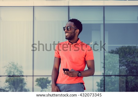 Afro american male in red t shirt texting sms on smartphone.