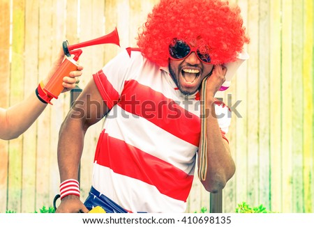 Afro american man fan of football have fun with bizarre look for international sport event - Black african male with funny wig is screaming deafened by unpleasant noise - Concept of health danger - stock photo