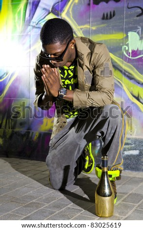 afro-american man offers prayers in front of colorful graffiti wall - stock photo