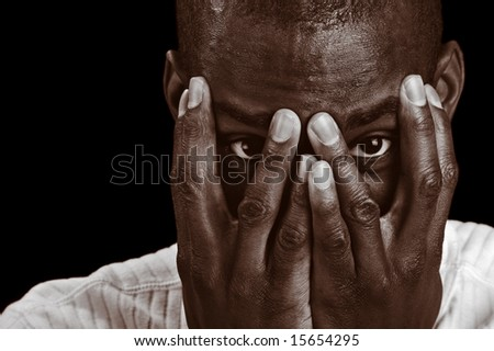 Afro-American man with hands up to his face but peeking though his fingers. - stock photo