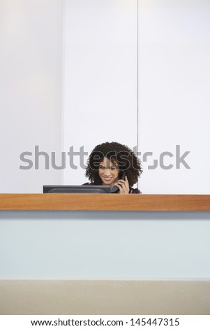 Afro American receptionist talking on telephone and using computer behind reception desk  - stock photo