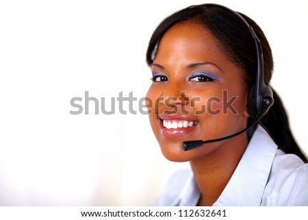 Afro-american secretary smiling at you with headphones - copyspace - stock photo