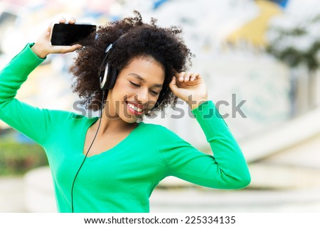 Afro-American woman listening to music  - stock photo