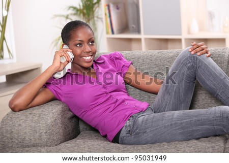 Afro-American woman on the phone laid on a sofa