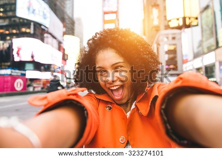 afro american woman taking selfie in Time square, New york. crazy portrait in the famous american square - stock photo
