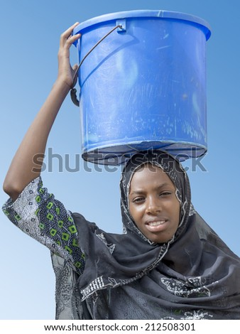 Afro beauty carrying a bucket of water on her head - stock photo