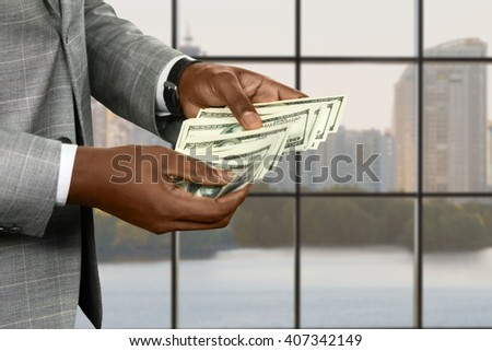 Afro businessman's hands counting cash. Manager with money at daytime. Think about sharing your wealth. Big city gives great opportunities. - stock photo