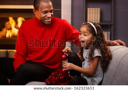 Afro father and beautiful little daughter sitting on sofa with christmas decoration, little girl laughing. - stock photo