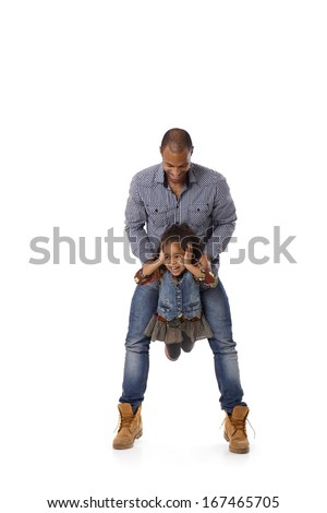 Afro father swinging little daughter between legs, little girl laughing.
