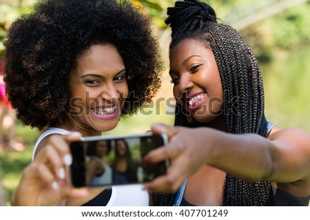 Afro friends having fun in the park taking selfie