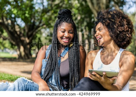 Afro friends using tablet in the park - stock photo