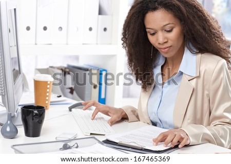 Afro office worker working with computer, typing on keyboard. - stock photo