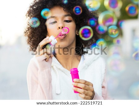 Afro woman blowing soap bubbles  - stock photo