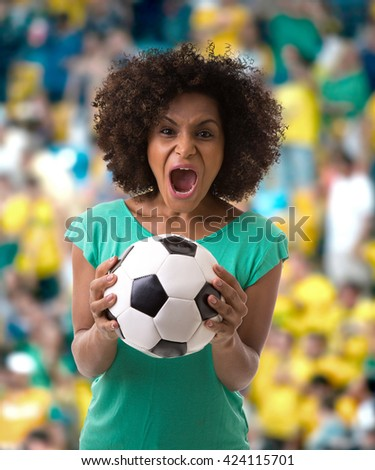 Afro woman holding a soccer ball in the stadium - stock photo