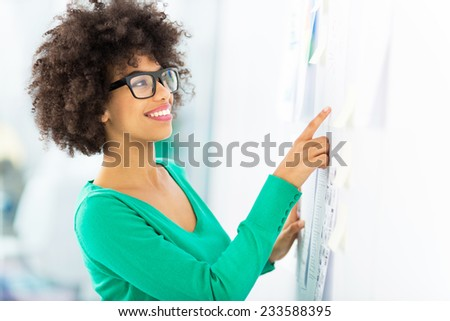 Afro woman looking at wall with adhesive notes - stock photo