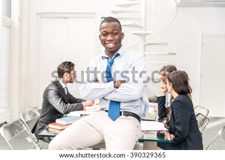 Afroamerican business man portrait - Team of businessmen in a conference meeting, confident young man smiling at camera with crossed arms - stock photo