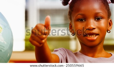 Afroamerican elementary schoolgirl with thumbs up in the classroom. - stock photo