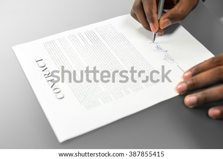 Afroamerican signs loan contract. Deciding to loan money. Gathering thoughts for decision. That's it. - stock photo