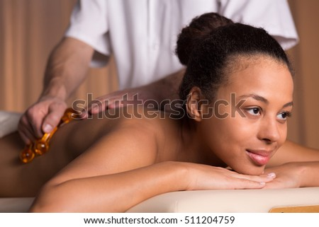Afroamerican woman having back massage in beauty salon