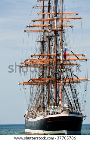 aft of sailboat going to open sea with sails down - stock photo