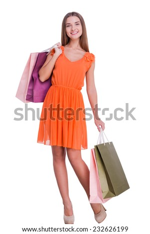 After a day shopping. Beautiful young woman holding shopping bags and smiling while standing against white background   - stock photo