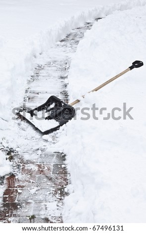after a heavy snowstorm. black shovel to remove the snow from the garden path. - stock photo
